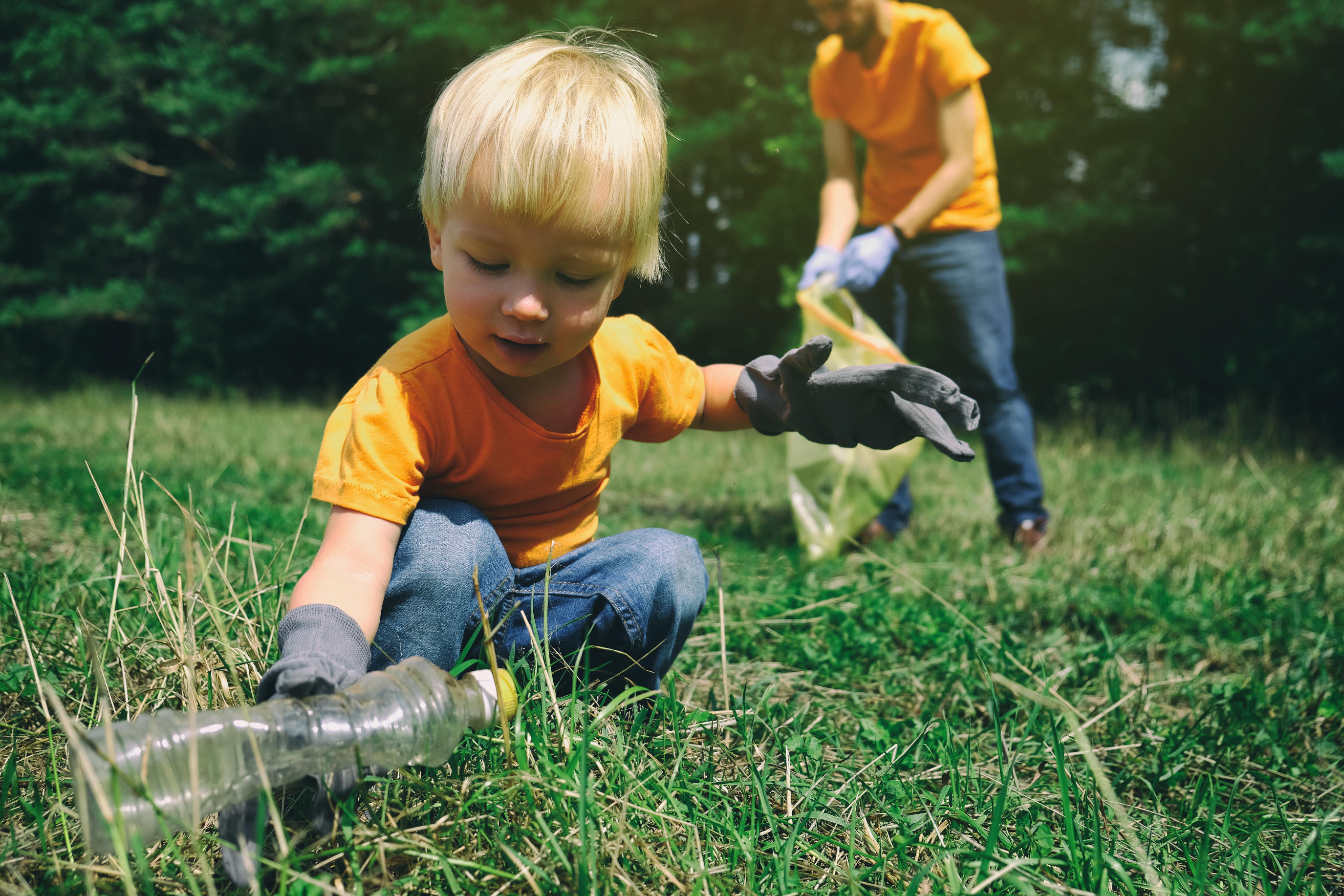 Volunteers activists child and his father in gloves tidying up rubbish in park or forest. Save environment concept. Stop plastic pollution